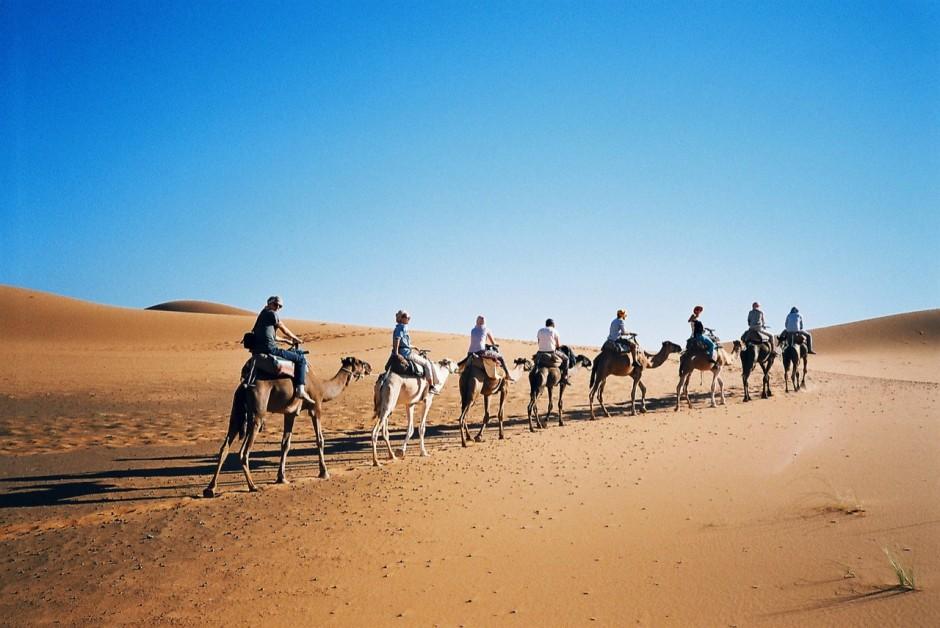 camel riding in sahara desert